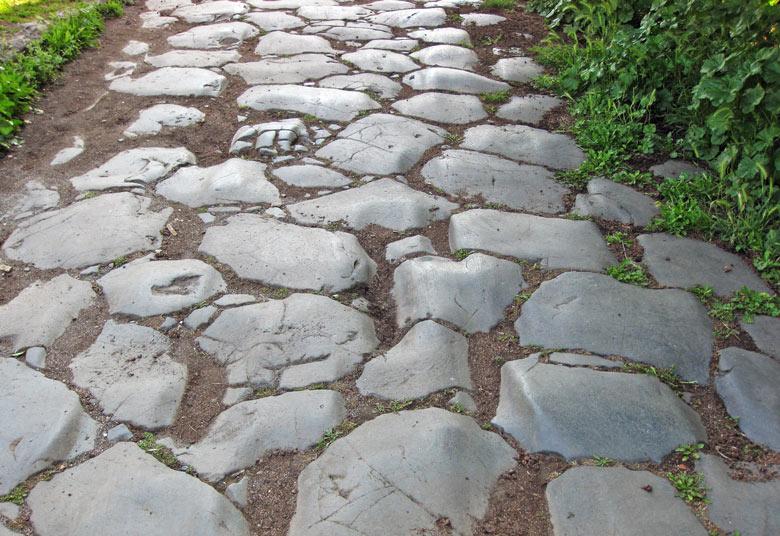 Römische Konsularstrasse mit massiven Decksteinen in offener Landschaft in Latium