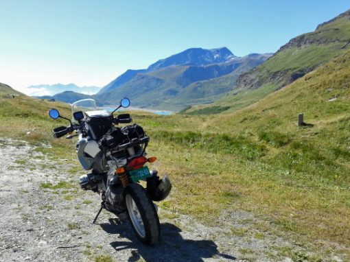 Bild von einem BMW-Motorrad am Mont Cenis mit dem Lac de Mont Cenis und einer Bergkette im Hintergrund