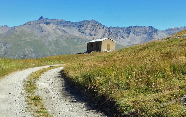 Bergkapelle am Mont Cenis mit einem Feldweg im Vordergrund und einer Bergkette im Hintergrund