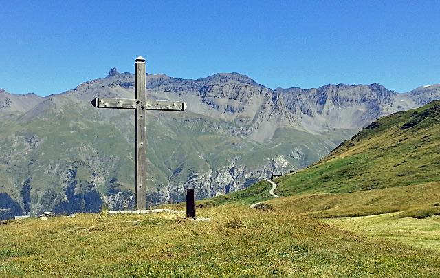 Gipfelkreuz auf dem Mont Cenis mit grünen Almwiesen und einer hohen Bergkette im Hintergrund