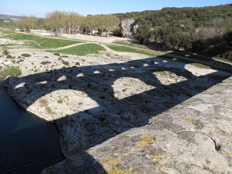 Schatten des Pont-du-Gard auf felsigem Flussgrund, gesehen auf einer Motorradtour durch Provence und Camargue