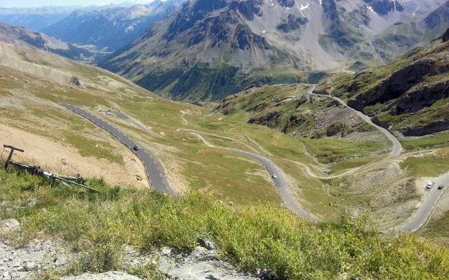 Auffahrt zum Col du Galibier mit Serpentinen talwärts und einem abgelegten Rennraf am Straßenrand