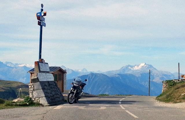 BMW R 1200 GS Motorrad am Col de la Madeleine, im Vordergrund die Ausschilderung der Passhöhe und der nächstgelegenen Ortschaften, im Hintergrund die teilweise verschneite Lauzère-Kette