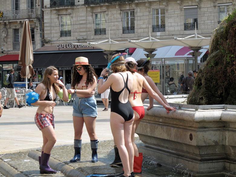 Junge Frauen im Bikini an einem Brunnen in Montpellier
