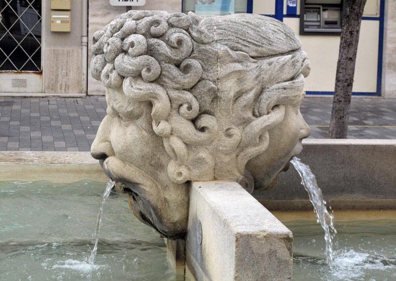 Janusbrunnen in Arles mit einem männlichen und einem weiblichen wasserspeienden Kopf