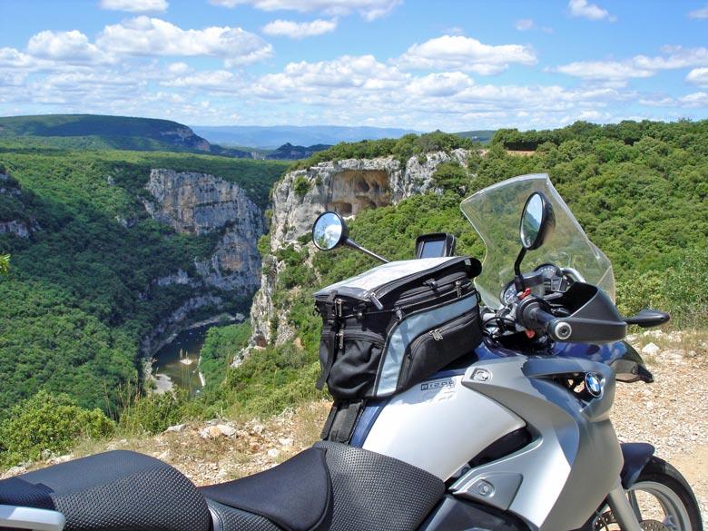 Bild von einer Panoramapause in den Gorges de l'Ardèche mit einem Motorrad BMW R 1200 GS im Vordergrund und einem weiten Blick in das tief eingeschnittene Flusstal
