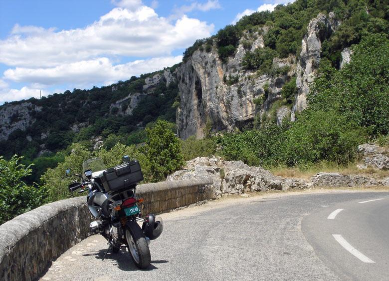 Bild von einer Kurvenstrecke in den Gorges de l'Ardèche mit einem Motorrad BMW R 1200 GS im Vordergrund