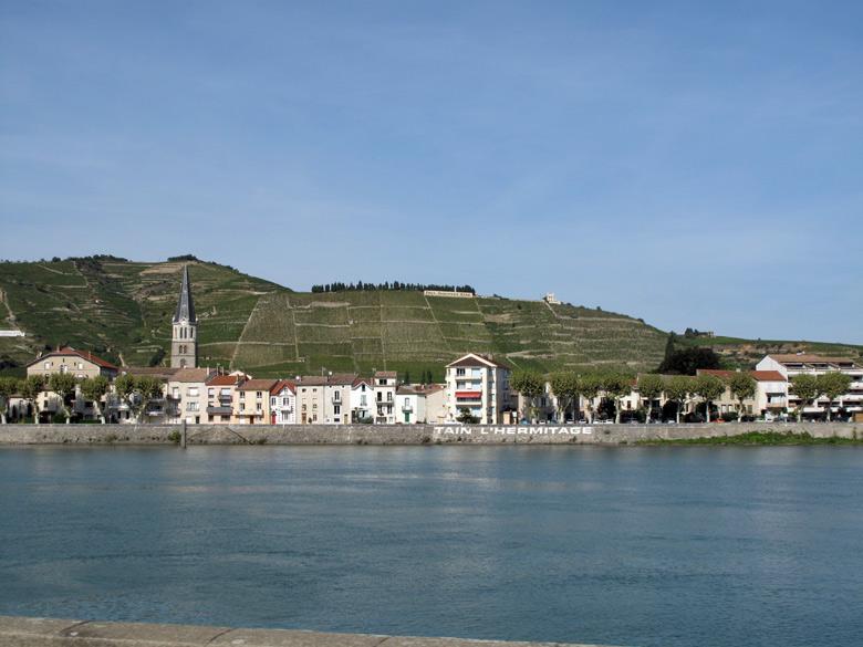 Bild vom Rhônetal bei Tournon mit dem Fluss im Vordergrund, der Stadt am Ufer und den Weinbergen des Tain l'Hermitage