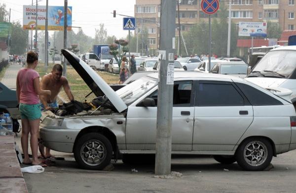 Bild von zwei Männern bei der Autoreparatur in Moskau auf dem Gehsteig mit einem Auto und offener Motorhaube