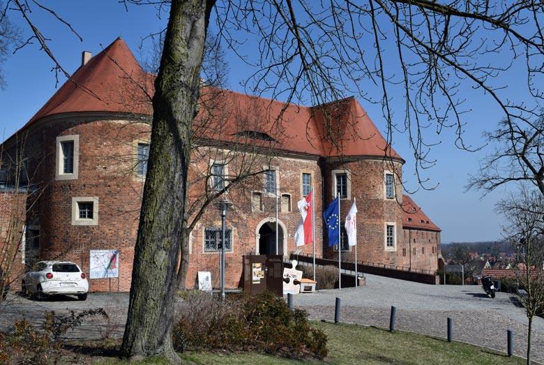 Bild der Burg Eisenhardt in Bad Belzig in Brandenburg mit einem Motorrad vor dem Burgtor