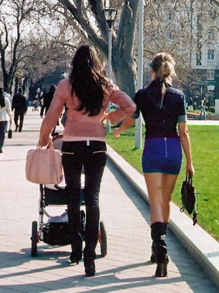 Bild von zwei Frauen in Russland mit sehr langen Beinen bei einem Frühlingsspaziergang, von denen eine einen Kinderwagen schiebt.