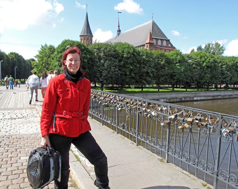 Rothaarige Motorradfahrerin mit roter Jacke vor dem Königsberger Dom