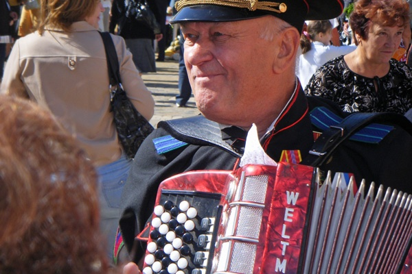 Bild von einem russischen Veteranen, der bei der Siegesfeier am 9. Mai Akkordeon spielt