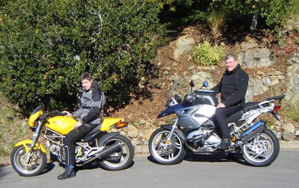 Bild von einem Mann auf einer blauen BMW R 1200 GS und seinem Sohn auf einer gelben Ducati Monster 750 vor der Ausfahrt