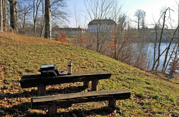 Schloss Meseberg von der Seeseite aus gesehen mit einer Holzbank in Vordergrund und einem Tankrucksack und einer Thermosflasche auf dem Tisch, gesehen bei einer Motorradtour im Land Ruppin