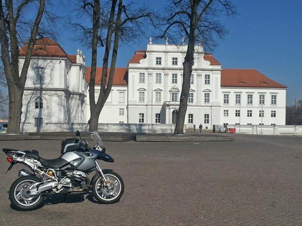 Bild von Schloss Oranienburg vom Schlossplatz aus mit einem blauen Motorrad BMW R 1200 GS im Vordergrund