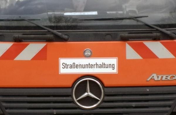 Orangefarbener LKW Daimler Atego mit dem Schild Strassenunterhaltung