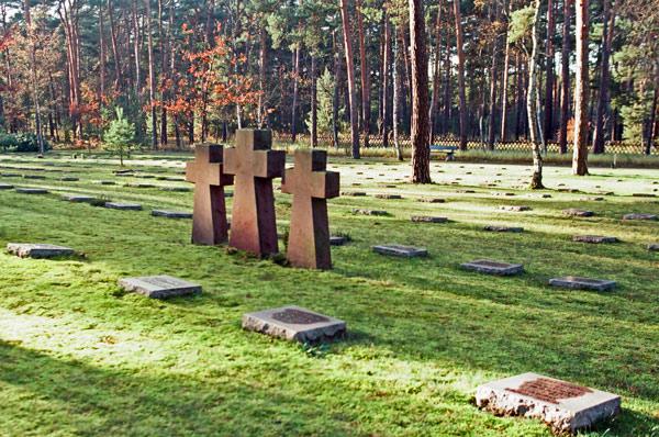 Bild vom Waldfriedhof Halbe bei Berlin mit drei steinernen Gedenkkreuzen und mehreren Reihen von Kriegsgräbern