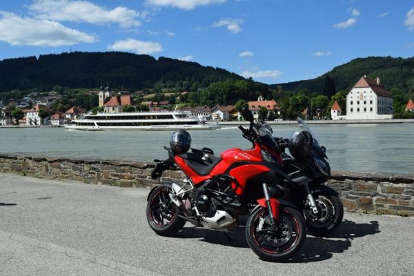 Bild einer Ducati Multistrada 1200 S und einer Yamaha FJR 1300 am Donauufer bei Obernzell mit einem Passagierschiff im Hintergrund