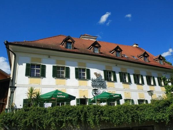 Bild von einem bayerischen Gasthaus an der Donau mit einem Wirtsgarten und grünen Sonnenschirmen