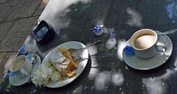 Bild von einem Teller mit hausgemachtem Apfelstrudel mit Sahne, zwei Fassen Kaffee und einem TomTom Urban Rider Navigationsgerät für Motorräder