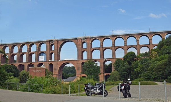Bild der Göltzschtalbrücke bei Netzschkau im Vogtland, der größten aus Backsteinen gebauten Eisenbahnbrücke der Welt, mit zwei Motorrädern im Vordergrund