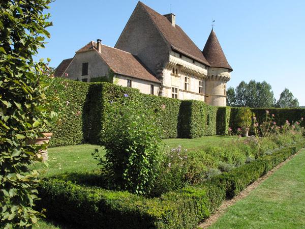 Bild vom Schloss Puymartin im Périgord in Südwestfrankreich mit Torhaus, Turm und Park