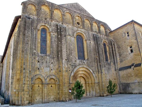 Bild von der Zisterzienserabtei Cadouin (Dordogne) aus gelbgrauem Sandstein mit zwei Kiefern neben dem Hauptportal, besucht bei einer Motorradtour Südwestfrankreich Teil 1
