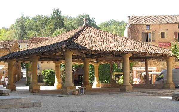 Bild der Markthalle in Cadouin (Dordogne), einem auf neun Säulen gestützten offenen Bau mit Ziegeldach und den umgebenden Häusern am Marktplatz