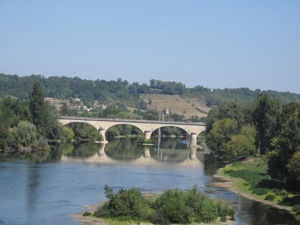 Bild vom Dordogne Übergang bei Ste-Foy-la-Grande in Südwestfrankreich mit einer Flussinsel im Vordergrund, einer Steinbrücke im Mittelgrund und dem Dorf im Hintergrund