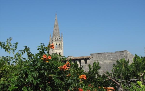 Bild der Kirche St-Emilion (Gironde) in Südwestfrankreich mit dem Kirchturm und einem orange blühenden Busch im Vordergrund