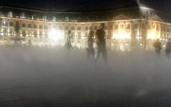 Bild von Bordeaux bei Nacht mit Wasserspielen an der Place de la Bourse mit dem erleucheten Börsengebäude und Fussgängern