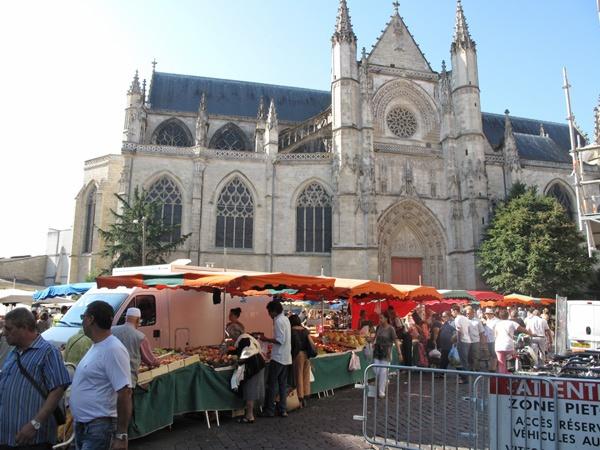 Bild vom Markttreiben vor der Kathedrale von Bordeaux mit Verkaufsständen, orange Sonnenschirmen, Lieferwagen und Kunden, die sich die Waren anschauen