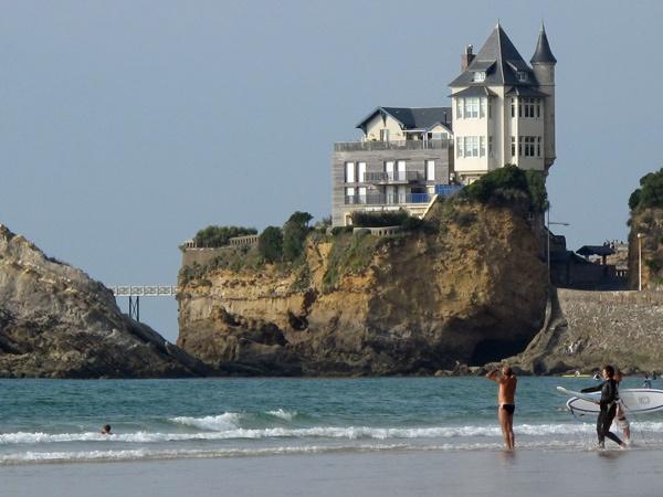 Bild einer Strandszene im Seebad Biarritz mit Surfern im Vordergrund vor einem grossen Felsen mit einem darauf gebauten Holzhaus