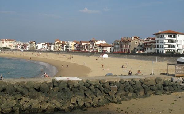 Ansicht vom Strand von St-Jean-de-Luz (Nouvelle Aquitaine) mit einer Steinmauer im Vordergrund, Badegästen und einer Häuserreihe hinter dem Strand