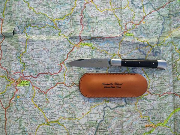 Bild von einem Yssingeaux-Messer mit Lederetui auf einer Landkarte der Auvergne mit dem Ort Yssingeaux, wo diese Messer hergestellt werden