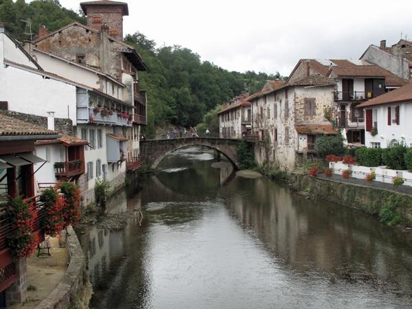 St-Jean-Pied-de-Port in den französischen Pyrenäen mit einer steinernen Bogenbrücke über den Fluss und alten Steinhäusern mit Blumen und Balkonen am Ufer