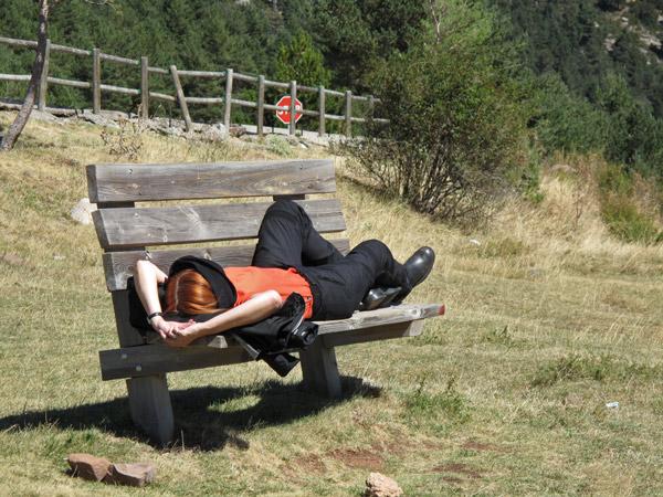 Rothaarige Motorradfahrerin mit orange T-Shirt und schwarzer Kombi auf einer Aussichtsbank ruhend