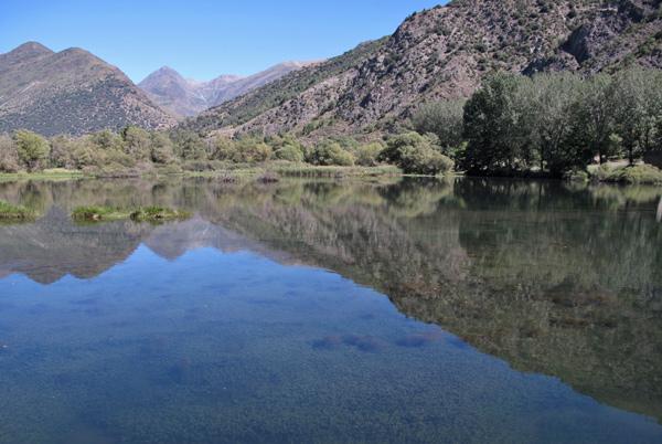 Pantè de la Torrassa in den katalanischen Pyrenäen, bei der sich die Berge im Hintergrund im tiefblauen Wasser spiegeln