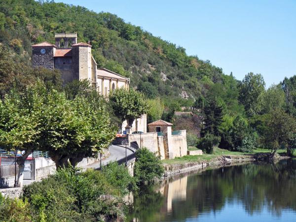 Dorfidylle an der oberen Garonne mit einer Strasse am Flussufer, einer Kirche und einem Wald am Steilhang