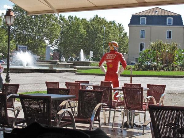 Bar Formule 1 in Carcassonne mit ausgefahrener Markise, Tischchen und Stühlen und einer Puppe mit rotem Rennfahrer-Schutzanzug