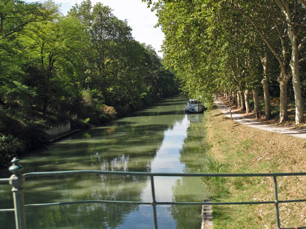 Canal du Midi südöstlich Toulouse mit einem festgemachten Kajütboot am Ufer, Platanenreihen beiderseits des Kanals und einem Brückengeländer