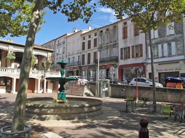 Place Verdun in Castelnaudary in Südwestfrankreich mit Brunnen, Platanen, einem Haus mit Laubengang, umstehenden Stadthäusern und geparkten Autos