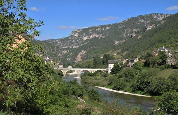 Ste-Enimie in den Gorges du Tarn mit Brücke über den Fluss Tarn und an die Felswände gebauten Häusern bei einer Motorradtour Südwestfrankreich Teil 2