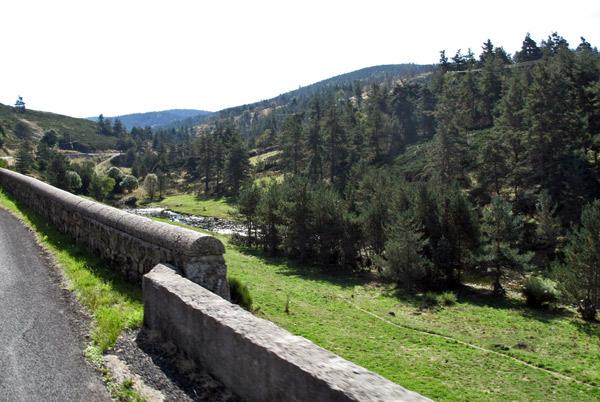 Tal der Espezonnette im Département Ardèche mit einer Teilansicht des Flusslaufes und dichten Wäldern zu beiden Seiten des Flussufers und Basaltfelsen