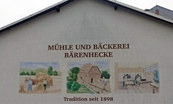 Mühlenbäckerei Bärenhecke im Müglitztal mit Wandmalereien über den Mühlen- und Bäckereibetrieb und der Aufschrift Tradition seit 1898