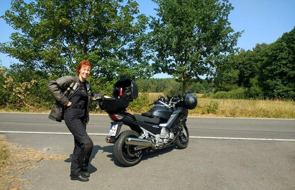 Rothaarige Motorradfahrerin mit einer dunkelgrauen Yamaha FJR 1300 am Strassenrand mit Wildobstbäumen im Hintergrund bei einer Motorradtour durch die Sächsische Schweiz