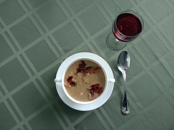 Suppentasse mit Maronensuppe und einer Auflage mit gebratenem Speck, daneben ein Suppenlöffel und ein Glas Rotwein