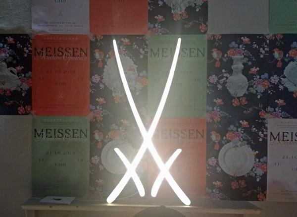 Bild der Meissener Schwerter als überdimensionales Leuchtobjekt vor bunten Werbeplakaten der Porzellanmanufaktur