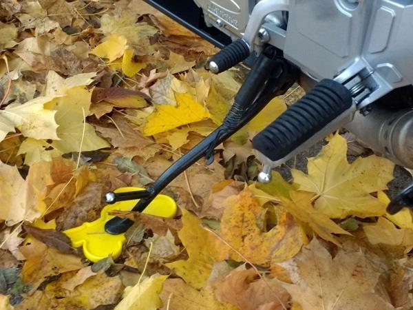 Untergelegte Stützplatte Plastik verhindert das Einsinken des Motorrad-Seitenständers in den aufgeweichten oder sandigen Boden.